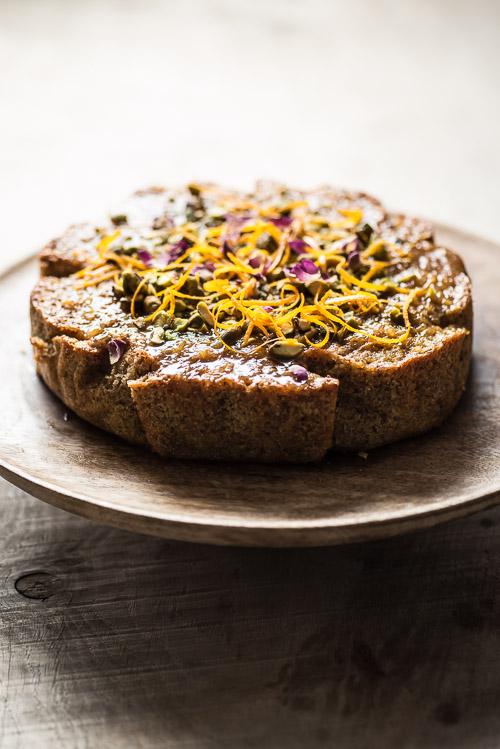Den færdige kage pyntet med appelsinskal, tørrede rosenblade og grofthakkede pistacienødder